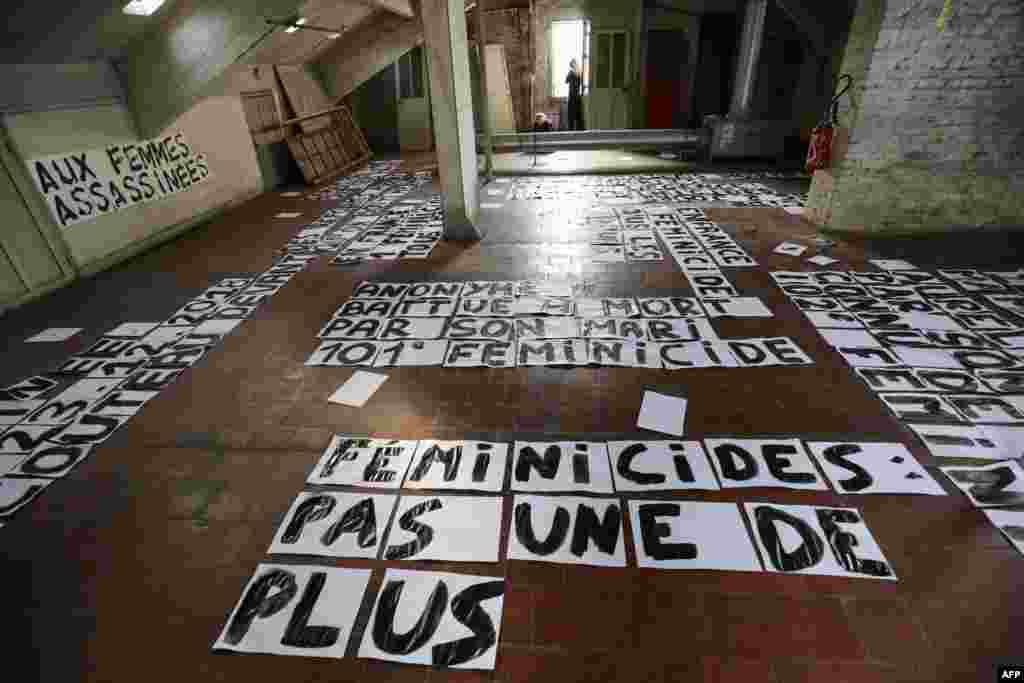 Banners to honor to the memory of women killed by romantic partners and against violence toward women are seen in an artist home in Paris.