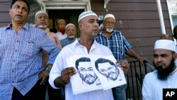 Members of the Al-Furqan Jame Mosque in Queens, New York, display a police sketch of a man suspected of shooting two clerics Saturday. Oscar Morel, 35, has been charged in the crime.