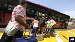 Deported Colombians prepare to board a bus that will take them to the border with Colombia, from San Antonio del Tachira, Venezuela, Aug. 25, 2015.
