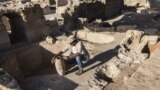 Avshalom Davidesko from the Israel's Antiquities Authority examines a jar in a massive ancient winemaking complex dating back some 1,500 years in Yavne, south of Tel Aviv, Israel, Monday, Oct. 11, 2021. (AP Photo/Tsafrir Abayov)