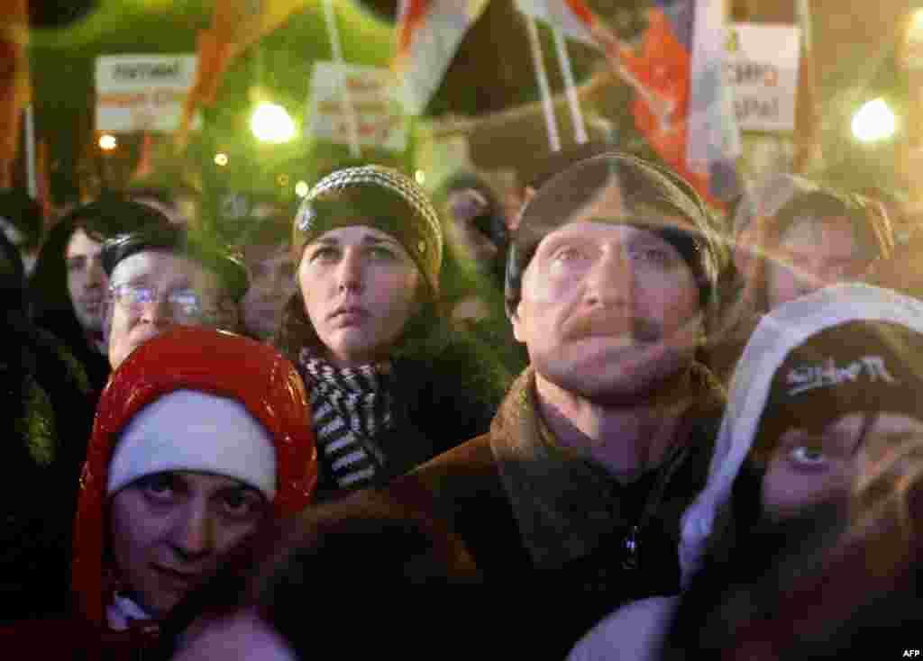 Người biểu tình nghe nói chuyện tại Moscow. Mấy ngàn người biểu tình chống Thủ tướng Vladimir Putin và đảng của ông. Đảng này chiếm nhiều ghế nhất trong cuộc bầu cử mà các nhà quan sát cho là gian lận. (AP/Ivan Sekretarev)