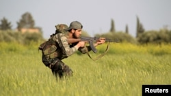 A rebel fighter is seen aiming his weapon in the countryside near Aleppo, Syria.
