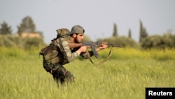 FILE - A rebel fighter is seen aiming his weapon in the countryside near Aleppo, Syria.