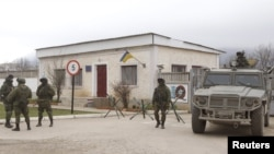 Những người vũ trang, được cho là lính Nga, canh gác bên ngoài một đơn vị quân đội của Ukraina ở làng Perevalnoye bên ngoài Simferopol, ngày 11/3/2014.
