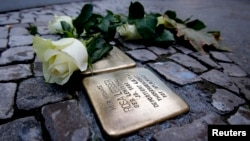 File - A rose lies beside a memorial stone commemorating Holocaust victim Rosa Lesser in front of her former home, Berlin.