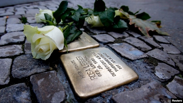 A rose lies beside a memorial stone commemorating Holocaust victim Rosa Lesser in front of her former home, Berlin, Nov. 9, 2013.