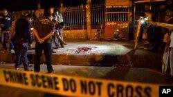 FILE - Bangladeshi policemen investigate at the site of attack on Bangladeshi-American blogger Avijit Roy, in Dhaka, Bangladesh, Feb. 26, 2015.