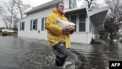 Rob Arneson nosi vreću sa peskom dok prolazi kroz poplavljeno područje u Lejkvilu, Masačusets