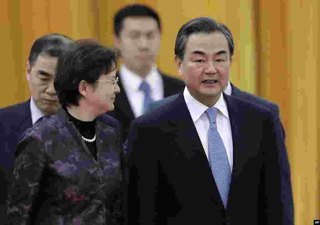 Menteri Luar Negeri China Wang Yi (kanan) berbincang dengan seorang delegasi saat menghadiri sebuah upacara. China mengatakan pada AS bahwa mereka menolak serangan dunia maya tapi tidak secara langsung mengutuk peretasan atas Sony Pictures (22/12). (AP/Andy Wong)