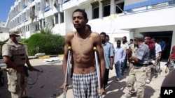 Gaddafi loyalists, taken prisoner by anti-Gaddafi fighters, are led out after they were found hiding in a hospital in the center of Sirte, October 9, 2011.