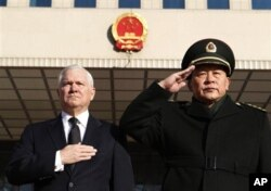 :中国国防部长梁光烈在北京举行的欢迎仪式上和时任美国国防部长的盖茨一起注目 聆听国歌(2011年6月5日)。