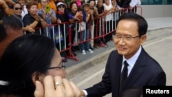 Former Thai prime minister Somchai Wongsawat greets supporters as he arrives at the Supreme Court in Bangkok, Thailand, Aug. 2, 2017.