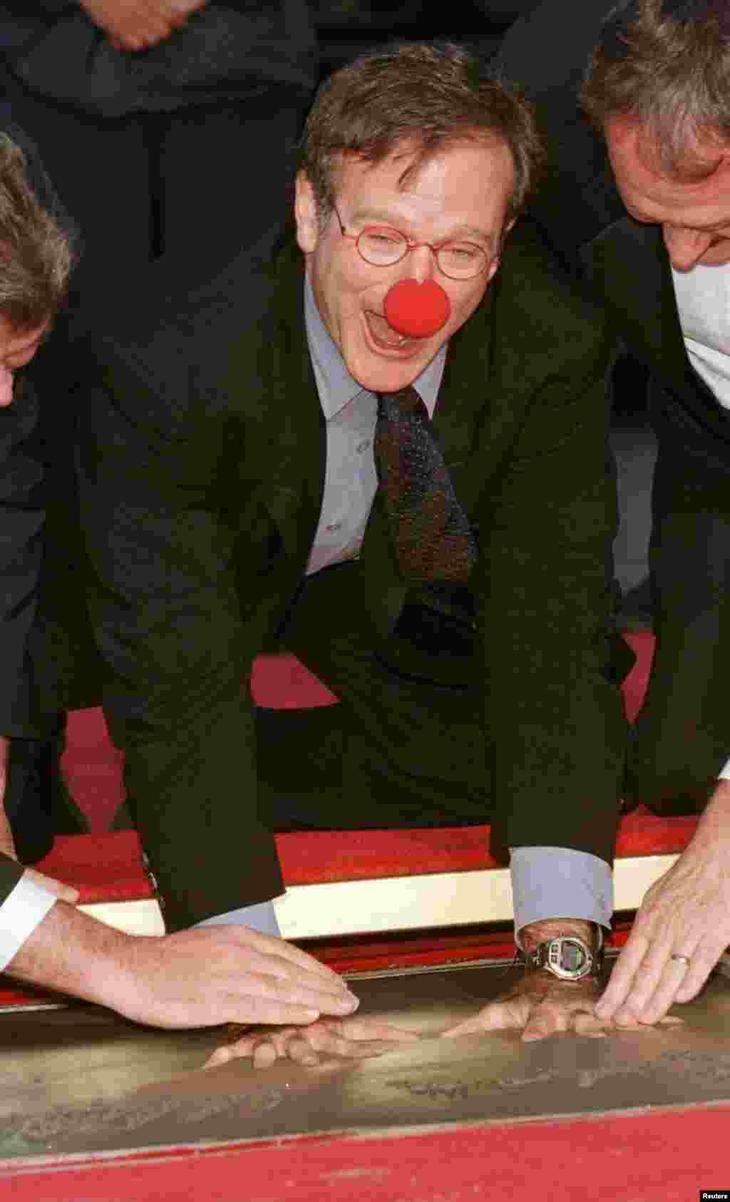 "Academy Award-winning actor Robin Williams, wearing a prop from his new film ""Patch Adams"" places his handprints in cement during ceremonies to honor him at Mann's Chinese Theater, in Hollywood, Dec. 22, 1998."