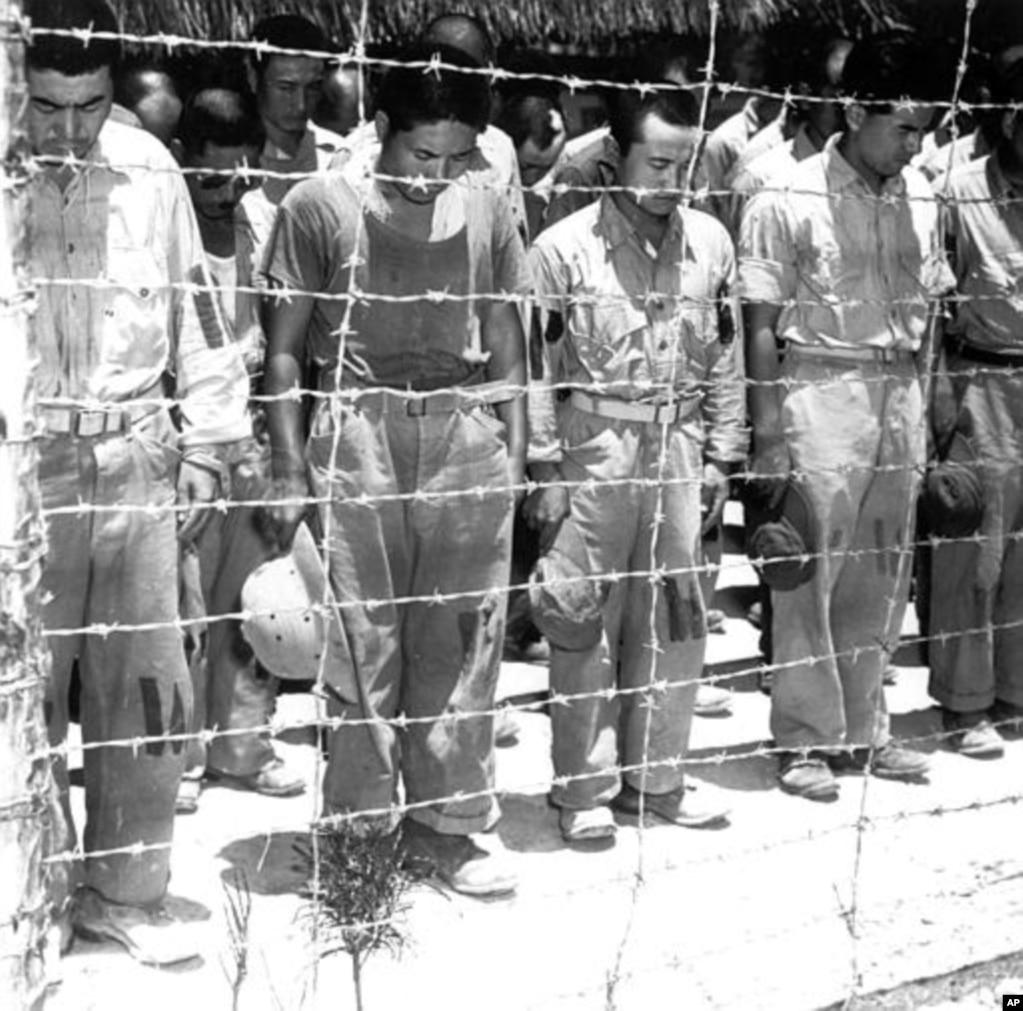 1945年8月15日,在马里亚纳群岛的关岛,日本战俘听到日本天皇宣布日本无条件投降的时候俯身鞠躬。