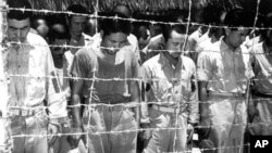 Japanese prisoners of war at Guam, Mariana Islands, bow their heads as they hear Japanese Emperor Hirohito making the announcement of Japan's unconditional surrender on August 15, 1945. (AP Photo)