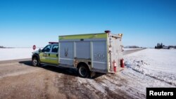 An emergency vehicle blocks the road to traffic the day after a bus carrying the Humboldt Broncos junior hockey team collided with a semitrailer nearby, near Tisdale, Saskatchewan, April 7, 2018.