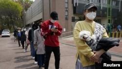 Warga Korea Selatan dengan tetap menjaga jarak dan mengenakan masker, antri untuk memberikan suara di sebuah TPS di Seoul, Rabu (15/4).