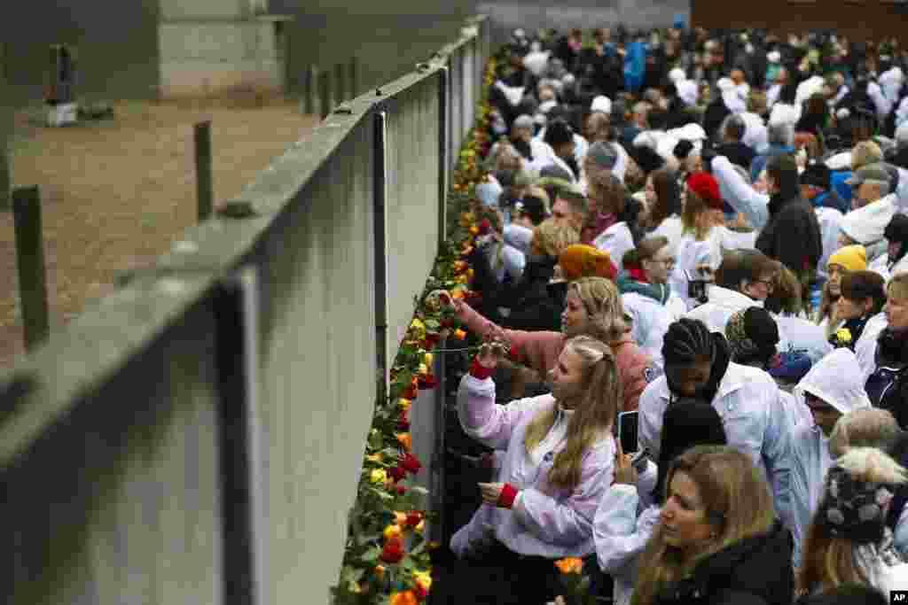 Berlində insanlar Berlin divarının sökülməsinin 30-cu ildönümündə divarın qalıqlarına güllər qoyub.