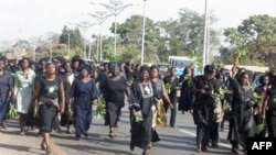 In this file photo, hundreds of women march through the streets to protest the killing of women and children and destruction of properties in Jos, Plateau State in central Nigeria. Hundreds of people have been killed in ethnic clashes in the area in recen