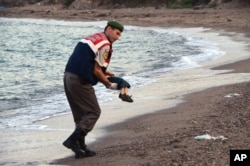 A paramilitary police officer carries the body of a migrant child after a number of migrants died and a smaller number were reported missing after boats carrying them to a Greek island of Kos capsized, near the Turkish resort of Bodrum, Sept. 2, 2015.