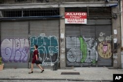 "In this May 31, 2017 photo, stores stand shuttered in downtown Rio de Janeiro, Brazil. The sign reads ""Rent"" in Portuguese."