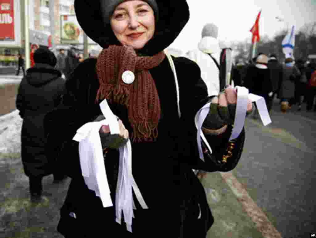 A protester hands out white ribbons at Saturday's protests. The ribbons have become a symbol of fair and honest elections, February 4, 2012. (VOA - Y. Weeks)