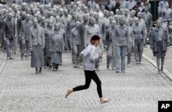 """Una mujer cruza la calle frente a una manifestación llamada """"1000 GESTALTEN"""", en la que miles de personas pintadas como figuras de barro avanzaban lenta y silenciosamente por las calles de Hamburgo para protestar contra la Cumbre del G20. Julio 7 de 2017."""