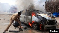 A man tries to extinguish a burning car after it exploded near Hamaerweyne market in Mogadishu, Somalia, July 24, 2013.