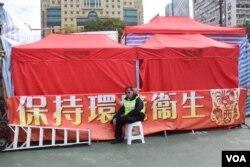 原本由青年新政及香港民族黨租用的3個維園年宵攤檔被食環署用紅色帳篷圍封,有職員看守。(美國之音湯惠芸攝)