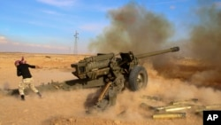 FILE - Syrian government troops fire at Islamic State group positions near Mahin, Syria, Jan. 30, 2016. Iran announced that it is bolstering its military presence in Syria.