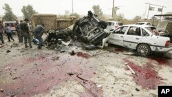 Bloodstains are seen on the ground near damaged vehicles at the site of a bomb attack in Kirkuk, 250 km (155 miles) north of Baghdad, May 19, 2011