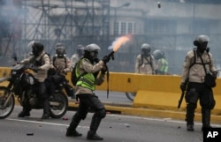 FILE - A police officer fires tear gas against anti-government protesters in Caracas, Venezuela, April 20, 2017.