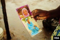 Esther Yakubu hold a photo of her daughter, Dorcas Yakubu, the Chibok girl who was featured in the Boko Haram video that was released today in Abuja, Nigeria, Aug. 13, 2016. (C. Oduah/VOA)