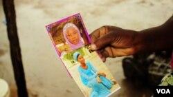 Esther Yakubu menunjukkan gambar putrinya, Dorcas Yakubu, gadis suku Chibok yang tampil di video Boko Haram, yang dirilis di Abuja, Nigeria, 13 Agustus 2016. (C. Oduah/VOA)