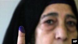 一名埃及婦女參加星期二的第三階段議會選舉投票後展示她手指上的印記。