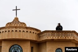A security member stands guard on the top of a church during a mass on Christmas Eve at the Mar Shimoni church in the town of Bartella, east of Mosul, Iraq, Dec. 24, 2016.