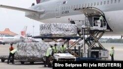 Pekerja mengenakan masker pelindung menurunkan Moderna hasil kerjasama internasional Indonesia-Amerika Serikat melalui fasilitas multilateral COVAX, di terminal kargo Soekarno Hatta International, 11 Juli 2021. (Foto: Courtesy Biro Pers via Reuters)