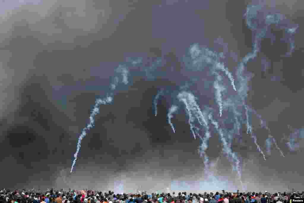 Tear gas canisters are fired by Israeli troops at Palestinian demonstrators during clashes at a protest demanding the right to return to their homeland, at the Israel-Gaza border in the southern Gaza Strip.