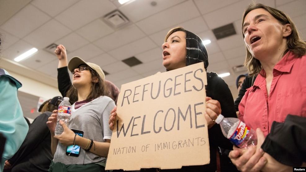 Một người phụ nữ cầm biểu ngữ ủng hộ di dân trong một cuộc biểu tình chống sắc lệnh về di trú của Tổng thống Trump, tại Sân bay Quốc tế Dallas/Fort Worth ở Texas, 28/1/2017.