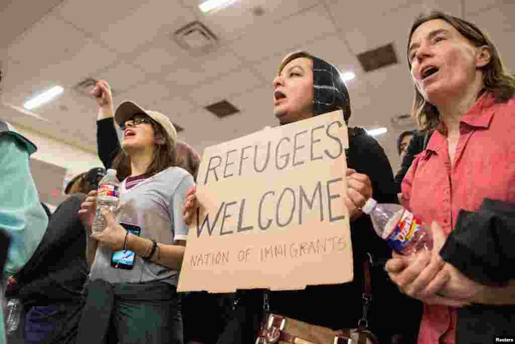 A woman holds a sign during a protest against the travel ban imposed by U.S. President Donald Trump's executive order, at Dallas/Fort Worth International Airport in Dallas, Texas, Jan. 28, 2017.