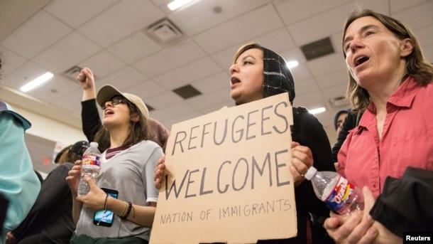 En el aeropuerto internacional de Dallas, Fort Worth, una mujer sostiene un cartel durante una protesta contra la prohibición de viajar impuesta por la orden ejecutiva del presidente estadounidense, Donald Trump.
