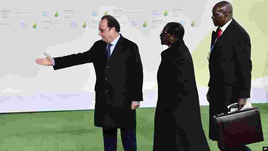 Le président Robert Mugabe du Zimbabwe est accueilli par son homologue français François Hollande, à gauche, à son arrivée à la COP21, au Bourget, 30 novembre 2015.