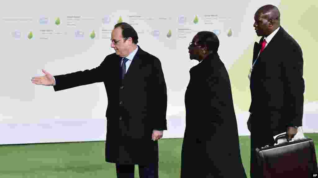 Rais wa Zimbabwe, Robert Mugabe (kati) akisalimiwa na Rais wa Ufaransa, Francois Hollande, (kushoto) alipowasili katika mkutano wa Dunia wa mabadiliko ya hali ya hewa mjini Le Bourget, nje ya Paris, Jumatatu, Novemba 30, 2015.