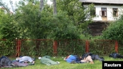 Migrants sleep in a park after a migrant camp burned in Velika Kladusa, Bosnia and Herzegovina
