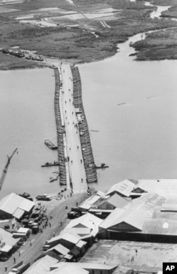 FILE - Military traffic is halted as U.S. Army engineers finish repairing a pontoon bridge damaged by a Viet Cong underwater mine, August 1968. Linking Saigon with the Mekong Delta, the bridge over the Oriental River replaced the permanent bridge, blown up by the enemy.