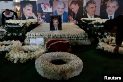 FILE - Wreaths and pictures of Lebanon's former Prime Minister Rafik al-Hariri are seen at his gravesite in downtown Beirut, Feb. 14, 2013.