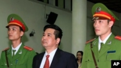 Cu Huy Ha Vu stands between policemen in front of the dock during his trial at a court in Hanoi, April 4, 2011.