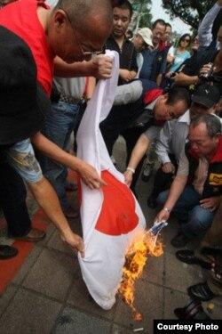抗议者在台湾立法院外焚烧日本国旗(中央社)