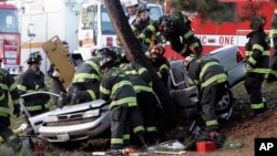 Seattle Fire Dept. firefighters swarm over a car as they work to cut passengers from the wreckage after the vehicle smashed into a tree just short of a pedestrian path at Green Lake park in Seattle, Thursday, Dec. 21, 2006. Three young men were critically injured in the crash, which closed northbound Aurora Avenue. (AP Photo/Elaine Thompson)