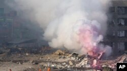 Smoke continues to rise hours after two explosions at a warehouse in Tianjin, China, August 12.